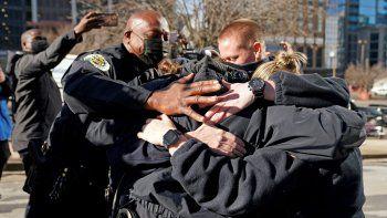 El jefe de la policía de Nashville, John Drake, izquierda, abraza a un grupo de agentes que a su vez se abrazan conmocionados tras hablar en una conferencia de prensa el domingo 27 de diciembre de 2020, en Nashville, Tennessee.