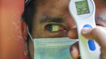 Un trabajador mide la temperatura de un hombre antes de permitirle ingresar al mercado de La Vega en medio de la pandemia del nuevo coronavirus en Santiago de Chile, el domingo 19 de julio de 2020.