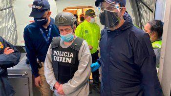 En esta foto proporcionada por la Oficina de Prensa de Migración de Colombia, el exjefe paramilitar Hernán Giraldo Serna, al centro, es escoltado al llegar al aeropuerto de El Dorado después de ser deportado desde Estados Unidos a Bogotá, Colombia, el lunes 25 de enero de 2021.