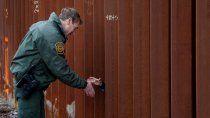 Rodney Scott, jefe del sector de San Diego de la Patrulla Fronteriza, estrechando la mano a otra persona a través de una sección del muro fronterizo, en San Diego.