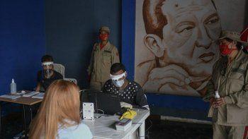 Personal del Consejo Nacional Electoral (CNE) con equipo protector del coronavirus revisa archivos en Caracas, Venezuela, con miras a las elecciones legislativas del 6 de diciembre. Detrás suyo hay una imagen de Hugo Chávez.