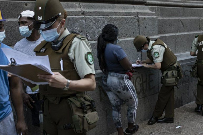 Mujeres policías dan información a los extranjeros para que inicien sus trámites de residencia en Santiago el 12 de abril de 2021