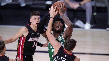 Kelly Olynyk (izquierda) y Duncan Robinson del Heat de Miami defienden mientras el base de los Celtics de Boston Marcus Smart trata de hacer un tiro durante la segunda mitad del juego de la NBA, el sábado 19 de septiembre de 2020, en Lake Buena Vista, Florida