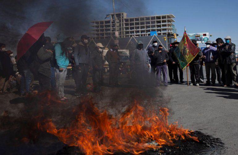 Manifestantes con tapabocas por el nuevo coronavirus queman un neumático durante una protesta contra el aplazamiento de las próximas elecciones presidenciales en El Alto