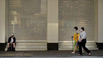 Tres mujeres pasan caminando junto a un hombre, sentado ante la entrada de un establecimiento, todos con mascarilla para frenar la propagación del coronavirus, en el último día de la cuarentena, en Pamplona, el 20 de junio de 2020.
