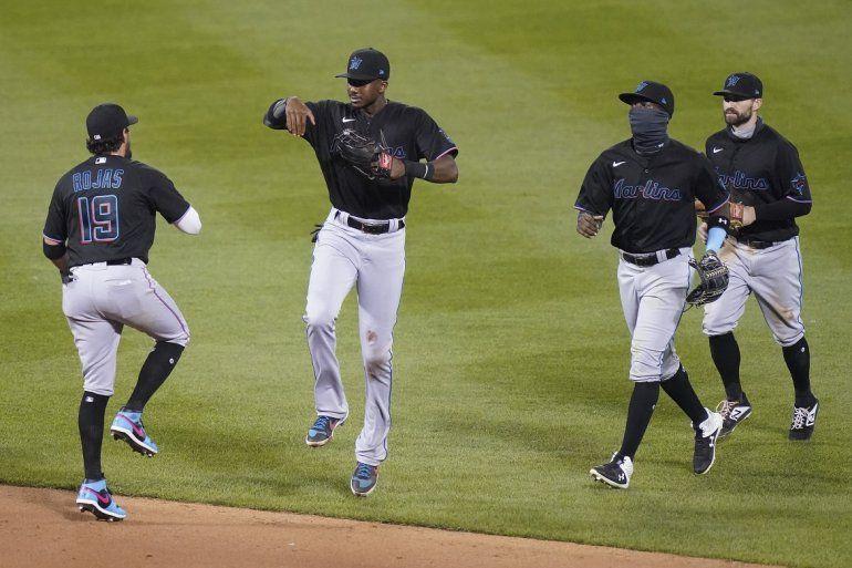 El campocorto de los Marlins de Miami Miguel Rojas (izquierda) celebra con sus compañeros la victoria en el segundo juego de una doble cartelera contra los Mets de Nueva York