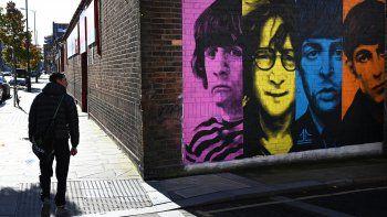 Los peatones pasan por un mural que representa a los miembros de la banda de rock británica The Beatles: Ringo Starr, John Lennon, Paul McCartney y George Harrison en el costado de un edificio en Liverpool, noroeste de Inglaterra, el 13 de octubre de 2020.