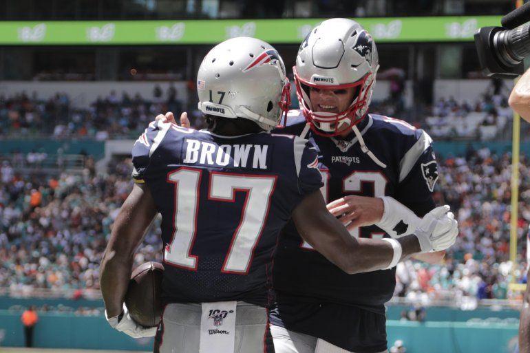 El quarterback de los Patriotas de Nueva Inglaterra Tom Brady y el wide receiver Antonio Brown celebran después del touchdown de Brown en la primera mitad del juego ante los Dolphins de Miami