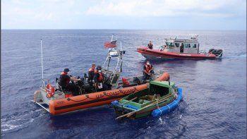 Dos embarcaciones de la Guardia Costera aparecen en la imagen junto a un bote en el que nueve cubanos intentaban llegar a las costas de EEUU. Archivo.