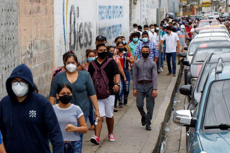 Los votantes hacen fila afuera de una mesa de sufragios durante las elecciones presidenciales y legislativas en Guayaquil