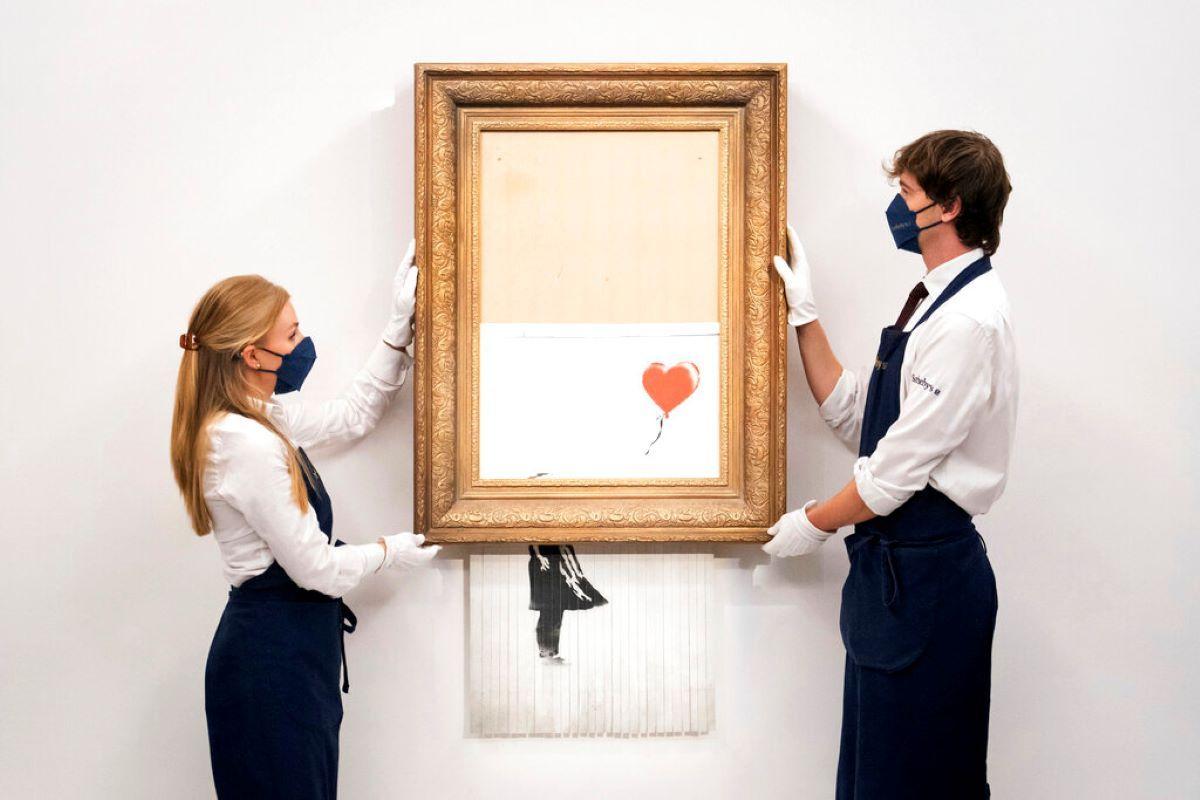 Manipuladores de arte sostienen Love is in the Bin de Banksy en la casa de subastas Sothebys en Londres.