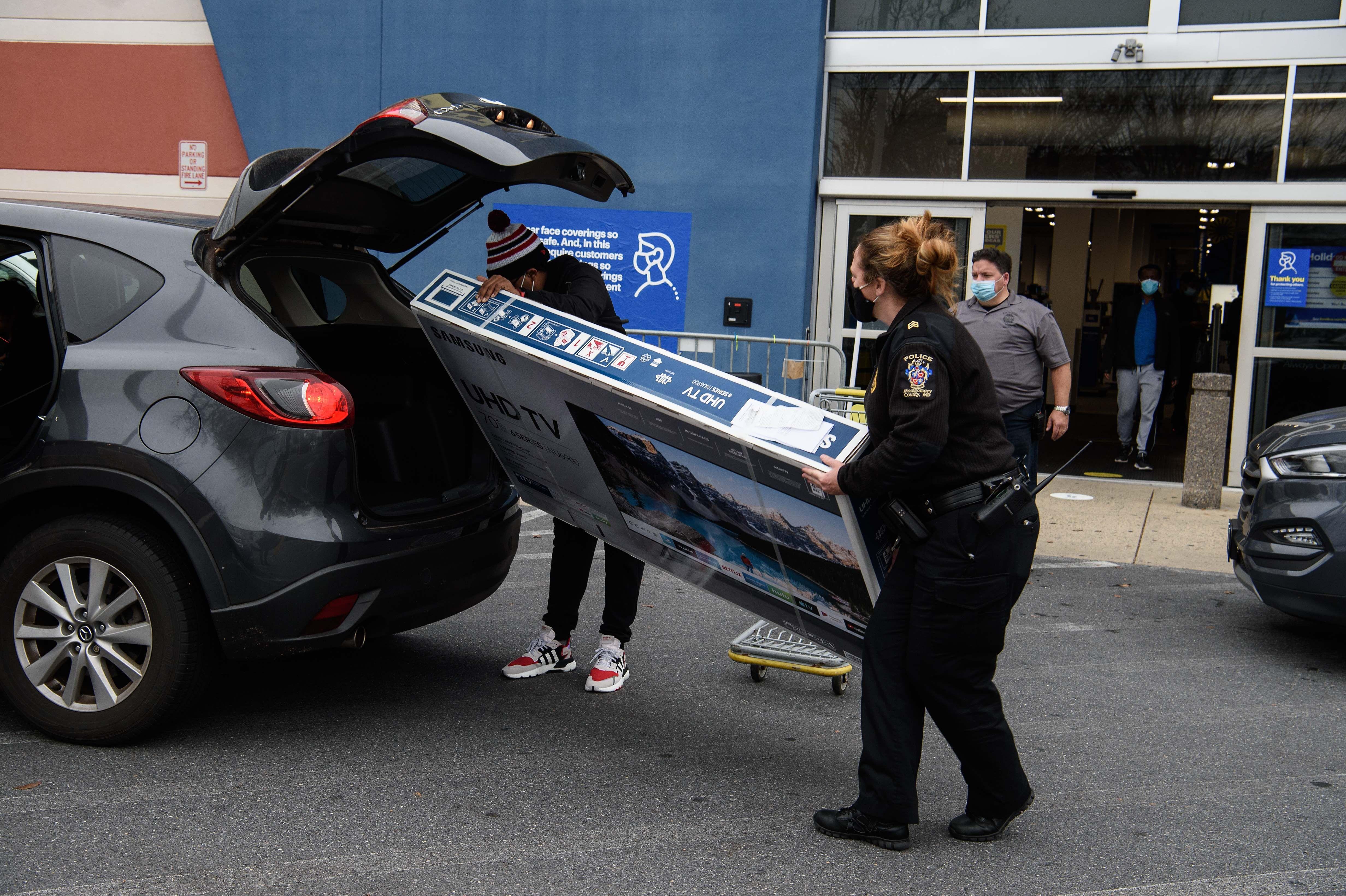 Un comprador es asistido para trasladar un televisor nuevo en su vehículo.