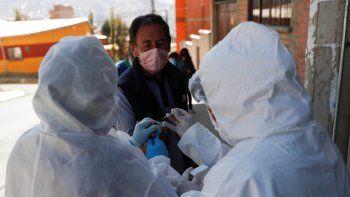Trabajadores de la salud vestidos con equipo de protección completo extraen sangre de un hombre para detectar el nuevo coronavirus durante una jornada de pruebas en el barrio de Villa San Luis de La Paz, Bolivia, el domingo 19 de julio de 2020. Un grupo de expertos, incluidos médicos, ha propuesto el aplazamiento de los comicios del 6 de septiembre debido a la crisis sanitaria.