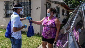Cathy Burgos, miembro del equipo de extensión comunitaria del condado de Miami-Dade, que distribuye bolsas que contienen máscaras, desinfectantes y guantes para educar a las personas sobre cómo mantenerse a salvo de COVID-19, en un barrio de Miami, Florida, el 30 de abril de 2020.
