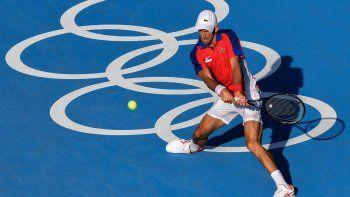 El serbio Novak Djokovic devuelve un tiro al boliviano Hugo Dellien durante el partido de tenis individual masculino de la primera ronda de los Juegos Olímpicos de Tokio 2020