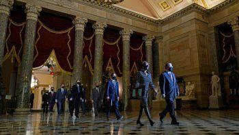 La secretaria de la Cámara de Representantes, Cheryl Johnson, junto con el sargento de armas en funciones Tim Blodgett, dirige a los fiscales de juicio político de la Cámara de Representantes para entregar al Senado el expediente de juicio político contra el expresidente Donald Trump, el lunes 25 de enero de 2021.