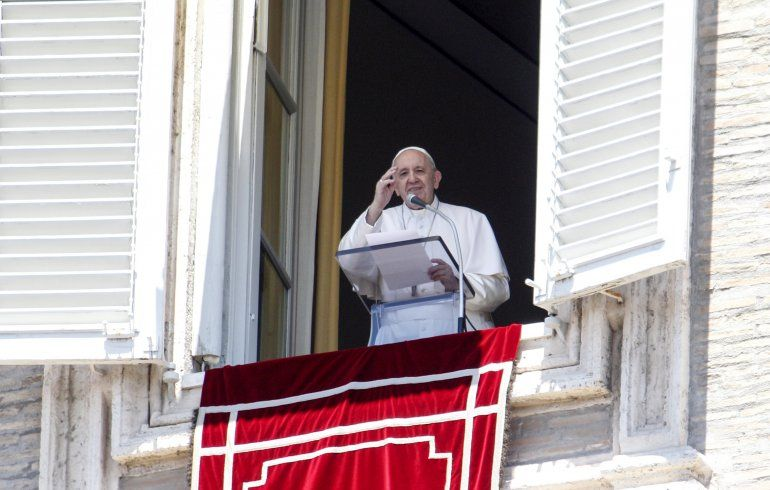 El papa Francisco saluda a feligreses desde la ventaja de su estudio con vista a la plaza de San Pedro en el Vaticano al terminar la oración del Angelus