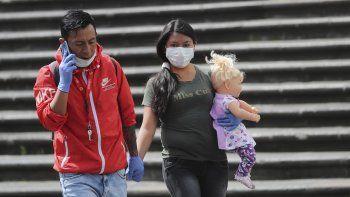 Una pareja con mascarillas y guantes para evitar el contagio del nuevo coronavirus camina de la mano por el centro de Quito, Ecuador, el viernes 10 de abril de 2020.