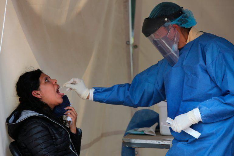 Un trabajador de la salud toma una muestra de la garganta de una mujer para hacer una prueba de detección de COVID-19 en Ciudad de México el sábado 10 de julio de 2021