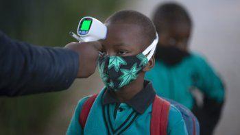 Un adulto comprueba la temperatura corporal de un alumno al regresar a la escuela en Johannesburgo, el martes 7 de julio de 2020, cuando se reabrieron más centros. Las escuelas habían cerrado en marzo en un intento de impedir contagios del nuevo coronavirus.