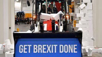 En esta foto de archivo tomada el 10 de diciembre de 2019, el primer ministro británico y líder del partido conservador Boris Johnson conduce un JCB con el tema de la bandera de la Unión, con las palabras Get Brexit Done dentro del cubo de la excavadora, a través de una pared falsa con la palabra GRIDLOCK.
