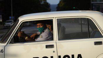 Agentes de policía con máscaras como precaución contra la propagación del nuevo coronavirus conducen una patrulla en una calle vacía durante el toque de queda en La Habana, Cuba, el martes 1 de septiembre de 2020.