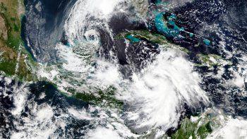 En esta imagen por satélite del 5 de octubre de 2020 proporcionada por NASA Worldview, Earth Observing System Data and Information System (EOSDIS), la tormenta tropical Gamma, a la izquierda, que castigó parte de México durante el fin de semana, y el huracán Delta, abajo a la derecha, que gana fuerza en un rumbo que lo llevará junto a las Islas Caimán el martes por la mañana.