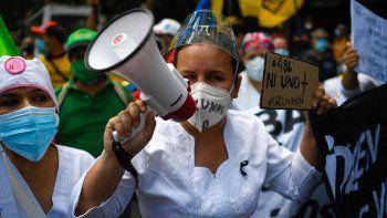 """En esta foto de archivo tomada el 17 de abril de 2021 una enfermera usa un megáfono y sostiene un cartel que dice """"486, ni uno más"""", en referencia a la cantidad de trabajadores de salud muertos, durante una protesta para exigir que se vacune a todo el personal de salud. contra COVID-19."""