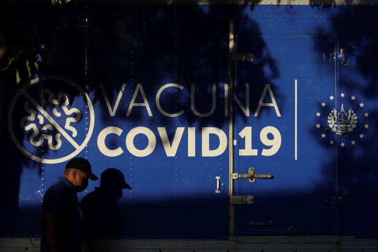 Un conductor pasa junto a un camión refrigerado del Ministerio de Salud que transporta dosis de vacunas para el COVID-19 que el gobierno de El Salvador donó a Honduras antes de partir de San Salvador