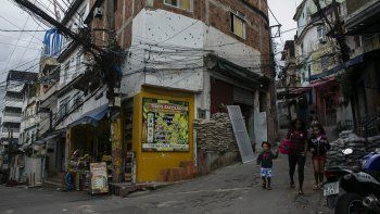 Unos residentes caminan frente a un edificio con orificios de bala días después de un operativo de la policía en la favela de Jacarezinho, en Río de Janeiro, Brasil, el sábado 8 de mayo de 2021.