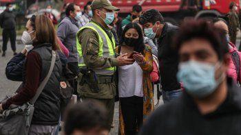 Un oficial de policía verifica los permisos de tránsito de las personas el jueves 1 de abril de 2021 en medio de una cuarentena por la pandemia de coronavirus afuera del Mercado Central, donde los compradores aguardan a comprar pescado para la Semana Santa, en Santiago, Chile.