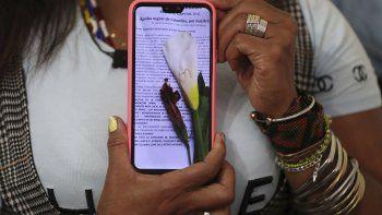 La líder comunitaria Luz Nelly Santana muestra una de las muchas amenazas de muerte que ha recibido en Bogotá, Colombia, el jueves 17 de diciembre de 2020. La líder comunitaria afrocolombiana a veces usa un sombrero o un turbante para disfrazarse y siempre lleva un chaleco antibalas.