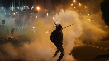 Un manifestante devuelve una lata de gas lacrimógeno lanzada por la policía para dispersar a inconformes el jueves 12 de noviembre de 2020, los cuales intentan aproximarse al Congreso en una protesta contra la remoción del presidente Martín Vizcarra, en Lima, Perú.