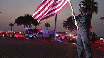 Homer Garza, bombero en Edinburg, ondea una bandera de Estados Unidos mientras los equipos de emergencias de la ciudad muestran su apoyo al personal médico y a sus pacientes, en el centro médico regional de Edinburg, el 22 de abril de 2020 en Edinburg, Texas.