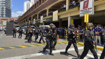 Un grupo de policías armados llega al centro comercial Greenhills el lunes 2 de marzo de 2002 en Manila, Filipinas, después de que se oyeran disparos en el interior.